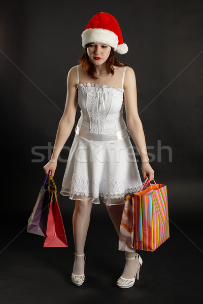 Comical tired woman in New Year's cap with purchases Stock photo © pzaxe