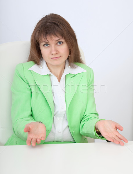 Woman sitting at table with astonishment makes helpless gesture Stock photo © pzaxe