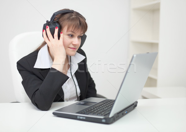 Woman in ear-phones sits with laptop at table at office Stock photo © pzaxe