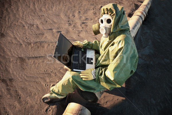 Scientist with laptop in zone of ecological disaster Stock photo © pzaxe