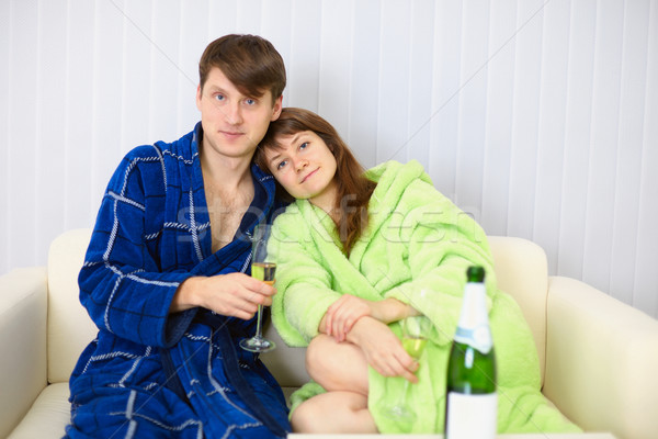 Young couple in dressing gowns sitting on couch with fizz Stock photo © pzaxe