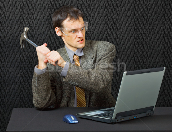 Comical person intends to break computer with hammer Stock photo © pzaxe