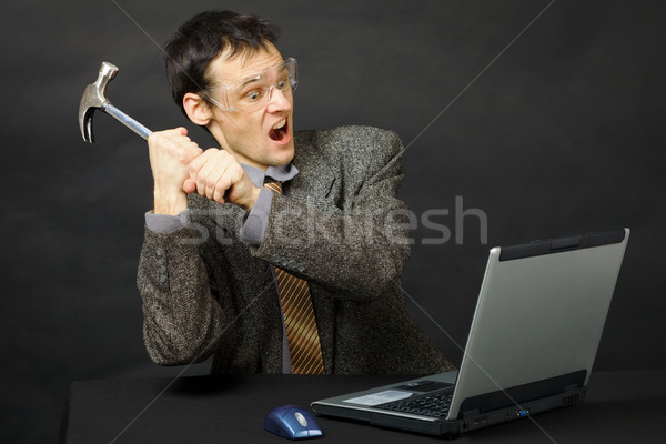 Furious young man breaks hammer computer Stock photo © pzaxe