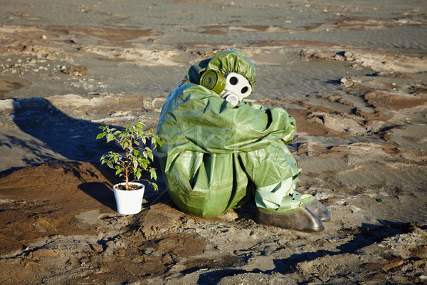 Man in chemical suit and houseplant in desert Stock photo © pzaxe