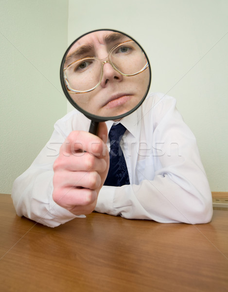 Stock photo: Man with a magnifier in a hand