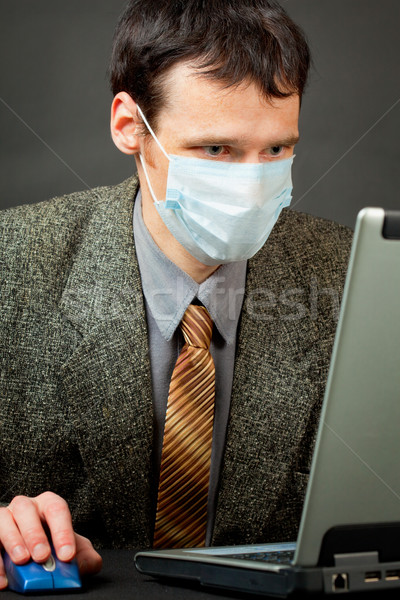 Man in medical mask works with laptop Stock photo © pzaxe