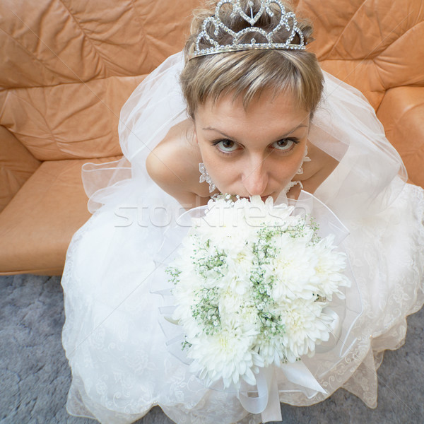 Amusing bride sits on sofa with bouquet - top view Stock photo © pzaxe