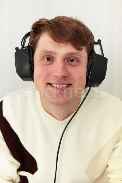 Cheerful guy with big ear-phones on a head Stock photo © pzaxe