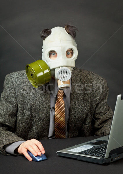 Amusing person has dressed gas mask and works with computer Stock photo © pzaxe