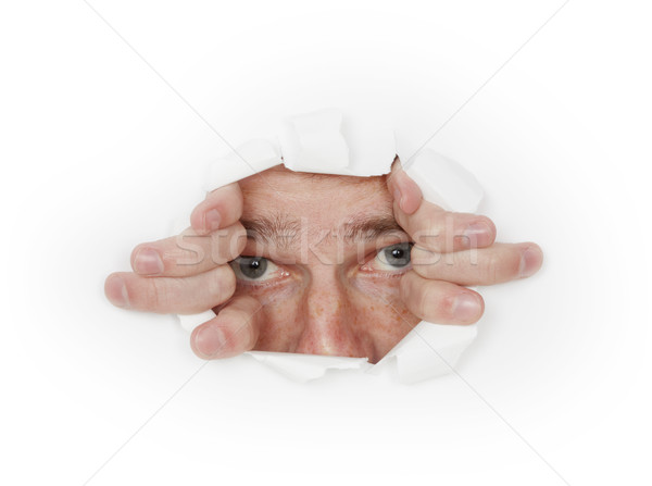 Man looks out from hole in white paper Stock photo © pzaxe