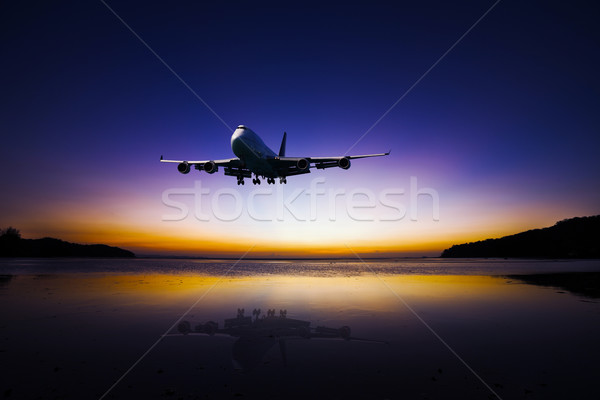 Airplane flying on colorful evening sky over sea at sunset with  Stock photo © pzaxe