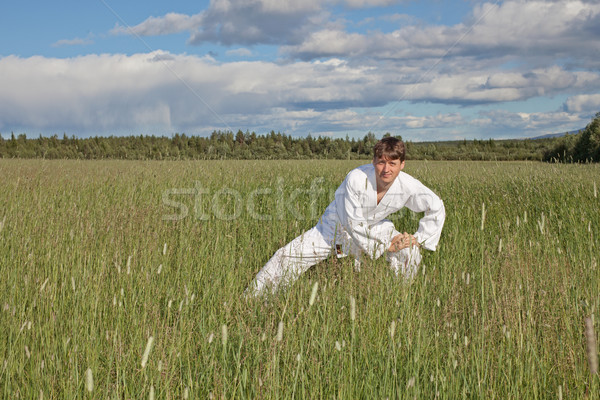 Young man practices Wushu in field Stock photo © pzaxe