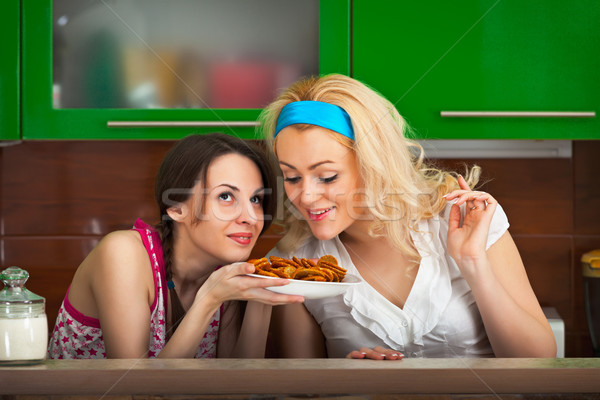 Girls try the freshly cooked homemade cookies Stock photo © pzaxe