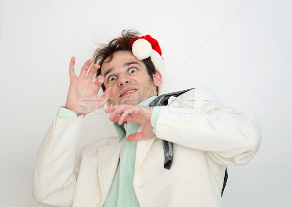 Amusing man in white suit and christmas cap is frightened Stock photo © pzaxe