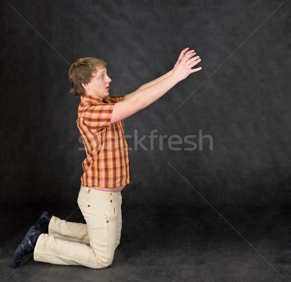 Amusing young man is kneeling and stretch hands to something Stock photo © pzaxe