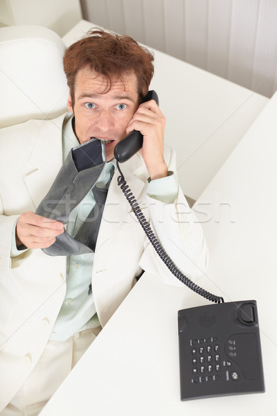 Young businessman speaks on phone, worries and bites tie Stock photo © pzaxe
