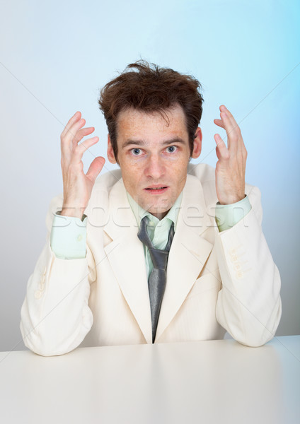 Young sorrowful man in white suit sits at table Stock photo © pzaxe
