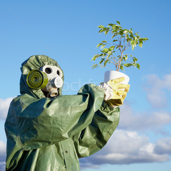 Man in chemical suit and gas mask with plant in hands Stock photo © pzaxe