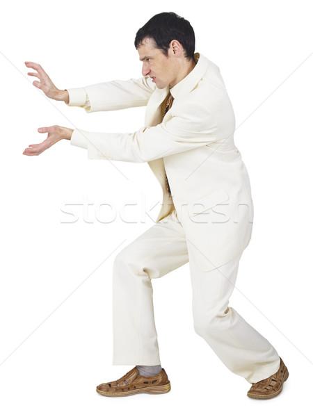 Amusing businessman pushes something forward Stock photo © pzaxe