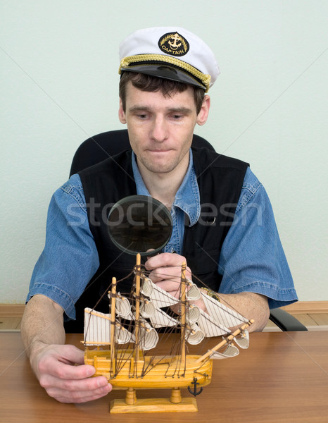 Guy in a sea cap with toy sailing vessel Stock photo © pzaxe