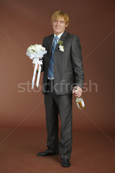 Groom with bouquet and bottle of sparkling wine Stock photo © pzaxe