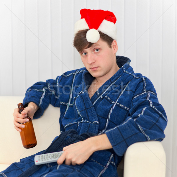 Man in Christmas cap with remote control and beer Stock photo © pzaxe