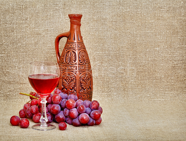 Clay jug with Georgian wine, glass and grapes Stock photo © pzaxe