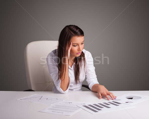 Businesswoman sitting at desk and doing paperwork Stock fotó © ra2studio
