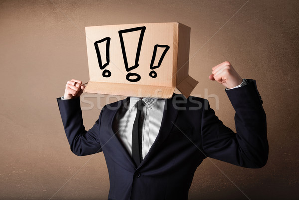 Businessman gesturing with a cardboard box on his head with excl Stock photo © ra2studio