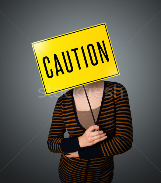 Young woman holding a caution sign Stock photo © ra2studio