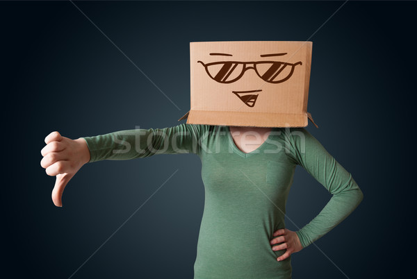 Stock photo: Young lady gesturing with a cardboard box on her head with smile