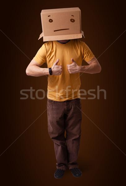 Fiatalember gesztikulál kartondoboz fej áll egyenes Stock fotó © ra2studio