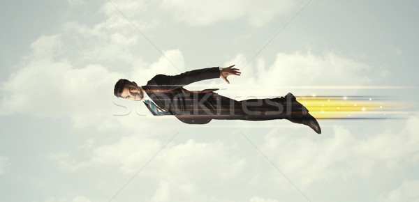 Happy business man flying fast on the sky between clouds Stock photo © ra2studio
