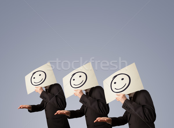 Men in suit gesturing with sketched smiley faces on cardboard Stock photo © ra2studio