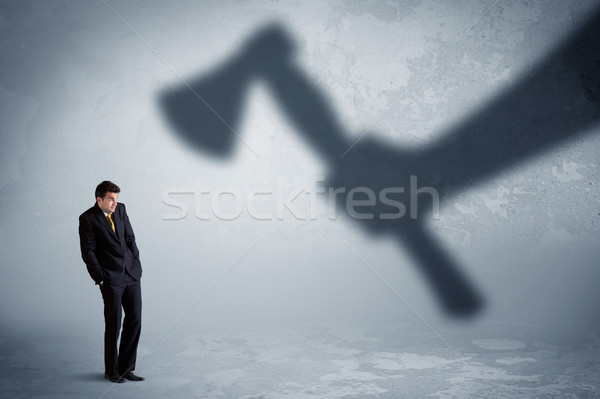 Businessman afraid of a huge shadow hand holding an axe concept Stock photo © ra2studio