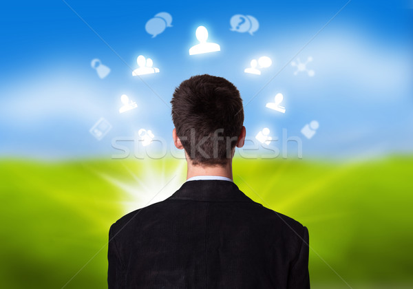 Stock photo: Young businessman with social network icons floating around his head 2
