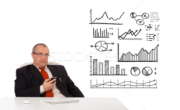 Businessman sitting at desk with diagrams and holding a mobilephone, isolated on white Stock photo © ra2studio