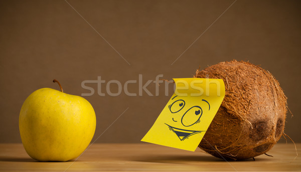 Stock photo: Coconut with post-it note looking curiously at apple