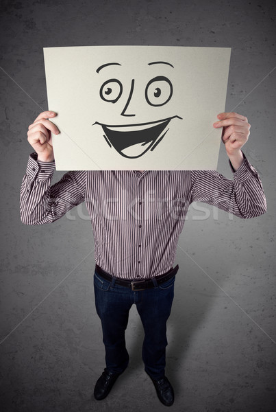 Businessman holding a cardboard with smiley face on it in front  Stock photo © ra2studio