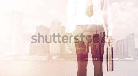 Businessman standing at cityscape background Stock photo © ra2studio