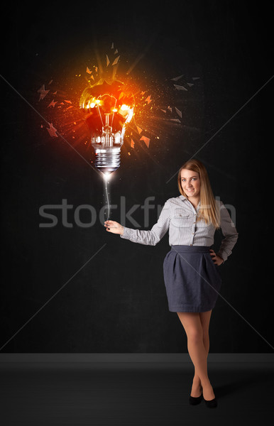 Businesswoman with an explosion bulb Stock photo © ra2studio