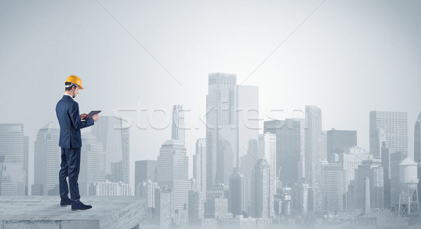 Architect standing on top of a maze and holding a plan Stock photo © ra2studio
