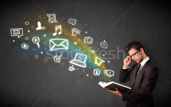 Stock photo: Businessman reading a book with multimedia icons coming out of the book