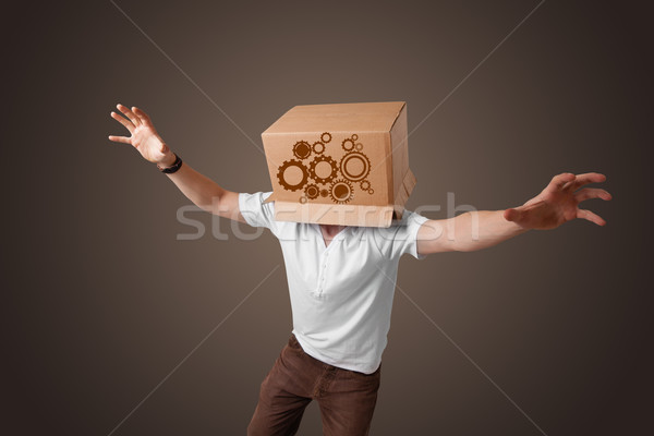 Young man gesturing with a cardboard box on his head with spur w Stock photo © ra2studio