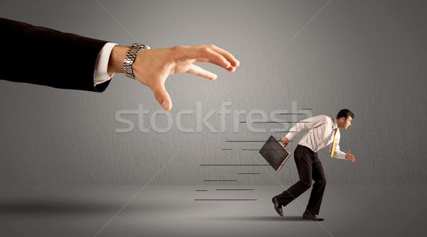 Businessman running away from a huge hand Stock photo © ra2studio