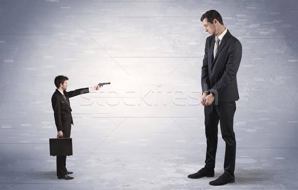 Small businessman shooting giant businessman Stock photo © ra2studio