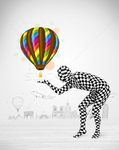 Stock photo:  man in full body suit holding balloon