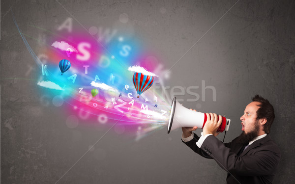 Man shouting into megaphone and abstract text and balloons come  Stock photo © ra2studio