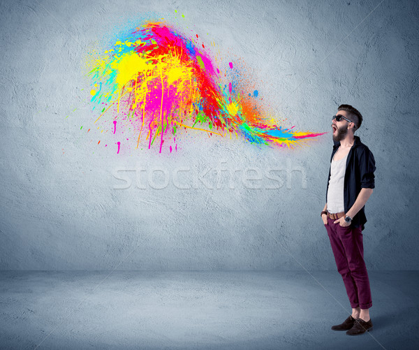Hipster guy shouting colorful paint on wall Stock photo © ra2studio