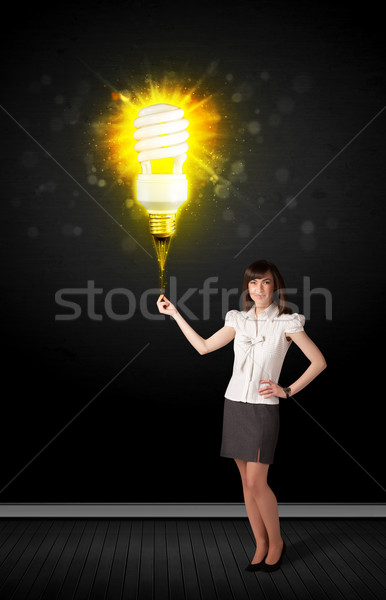 Businesswoman with an eco-friendly  bulb Stock photo © ra2studio